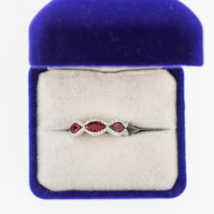 Shop Athena ring with three ruby stones with diamond halo setting in velvet blue box